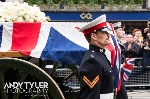Maggie's coffin passes by on a gun carriage, flanked by military personnel.