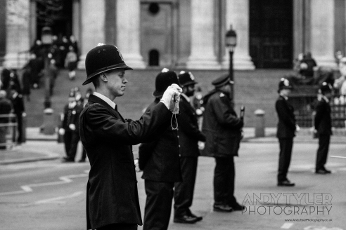 A policeman taks a photo of some members of the public.